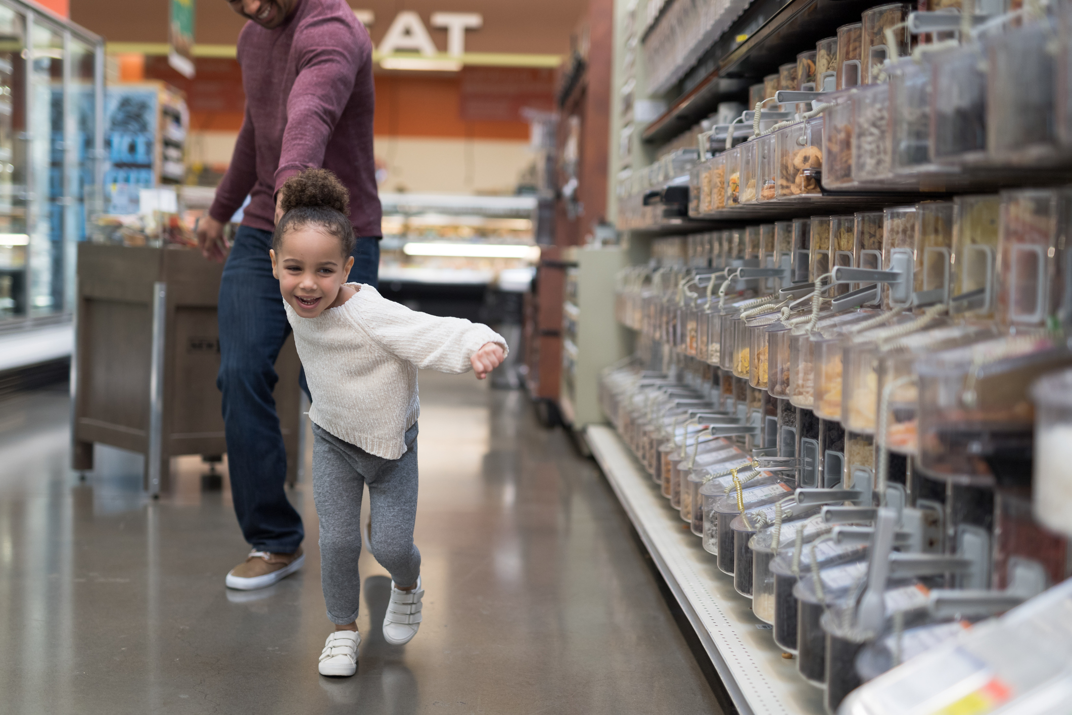 A pre-school age tugs her father along at the grocery store.