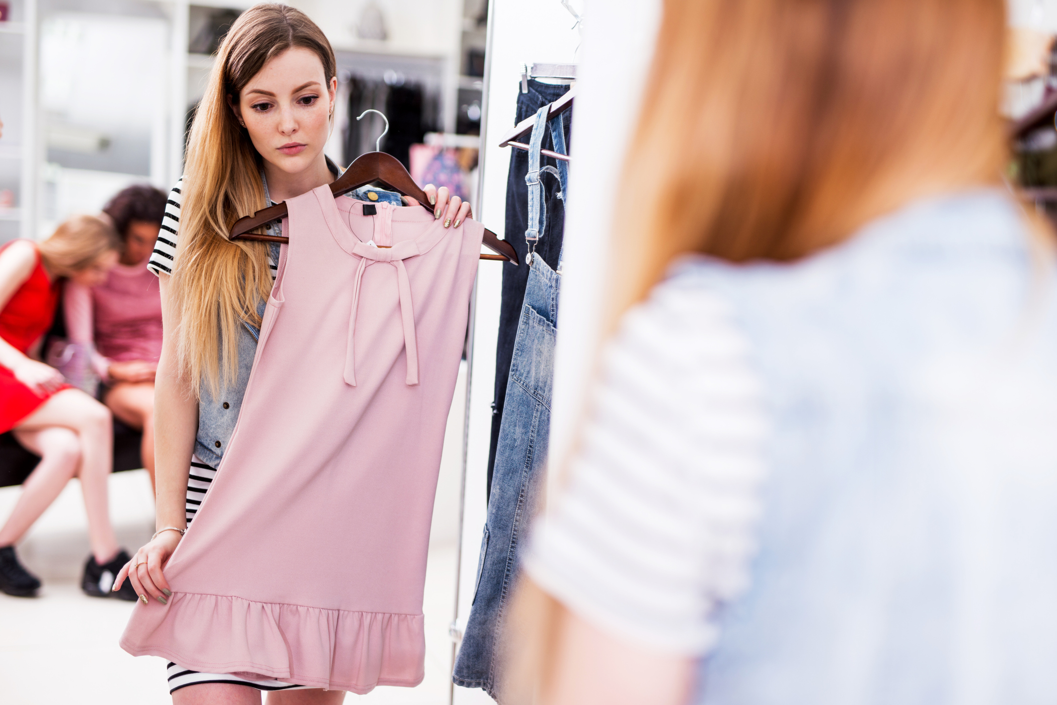 Young woman choosing new pink dress in a fashion boutique.